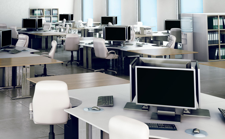Office desks with groups of monitors